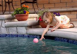 Young girl touching swimming pool water