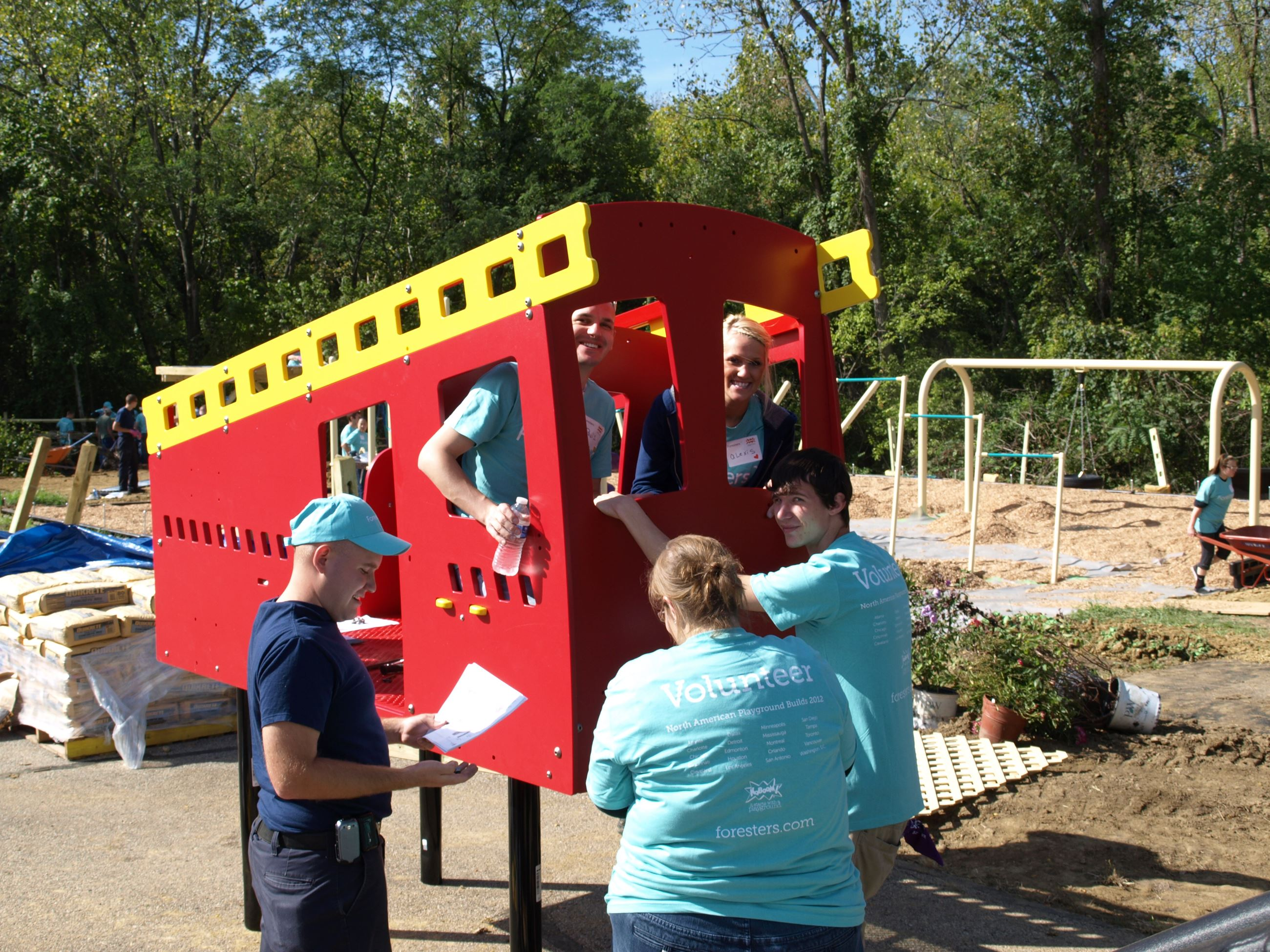 Workers smile as the install a vehicle feature at the playground at Pal Memorial Park